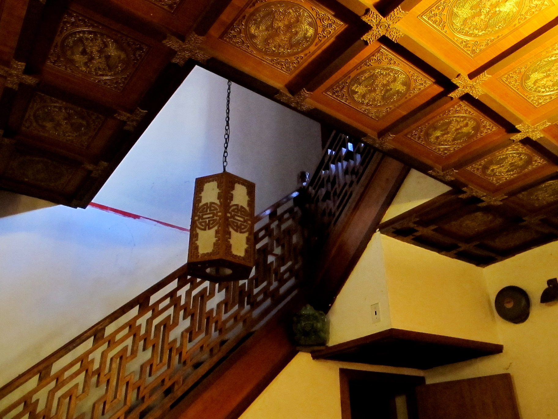 A painted, coffered ceiling and carved wooden railing are among the traditional elements of the stairhall.