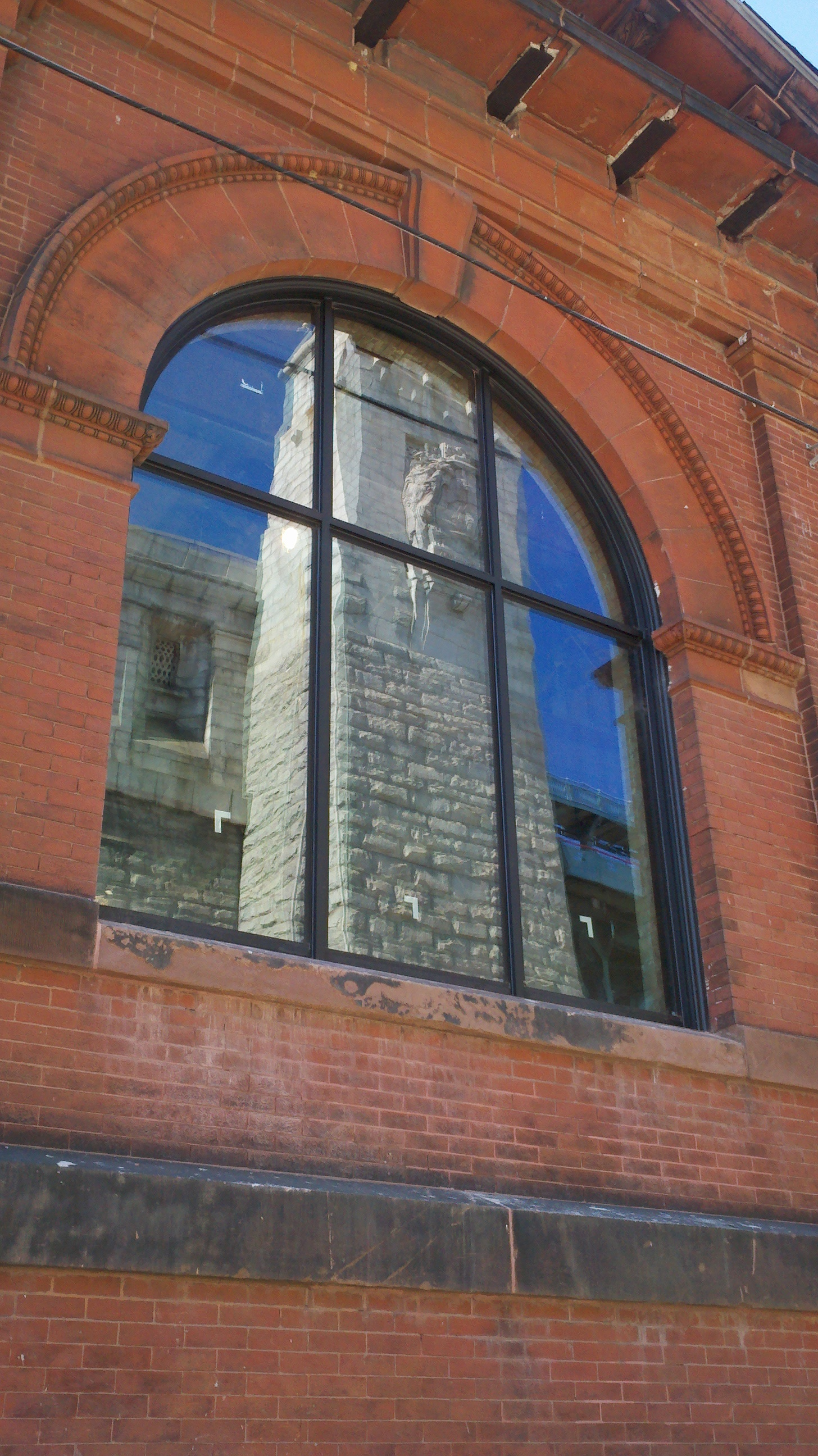 A tower of the Ben Franklin Bridge is reflected in a new FringeArts window