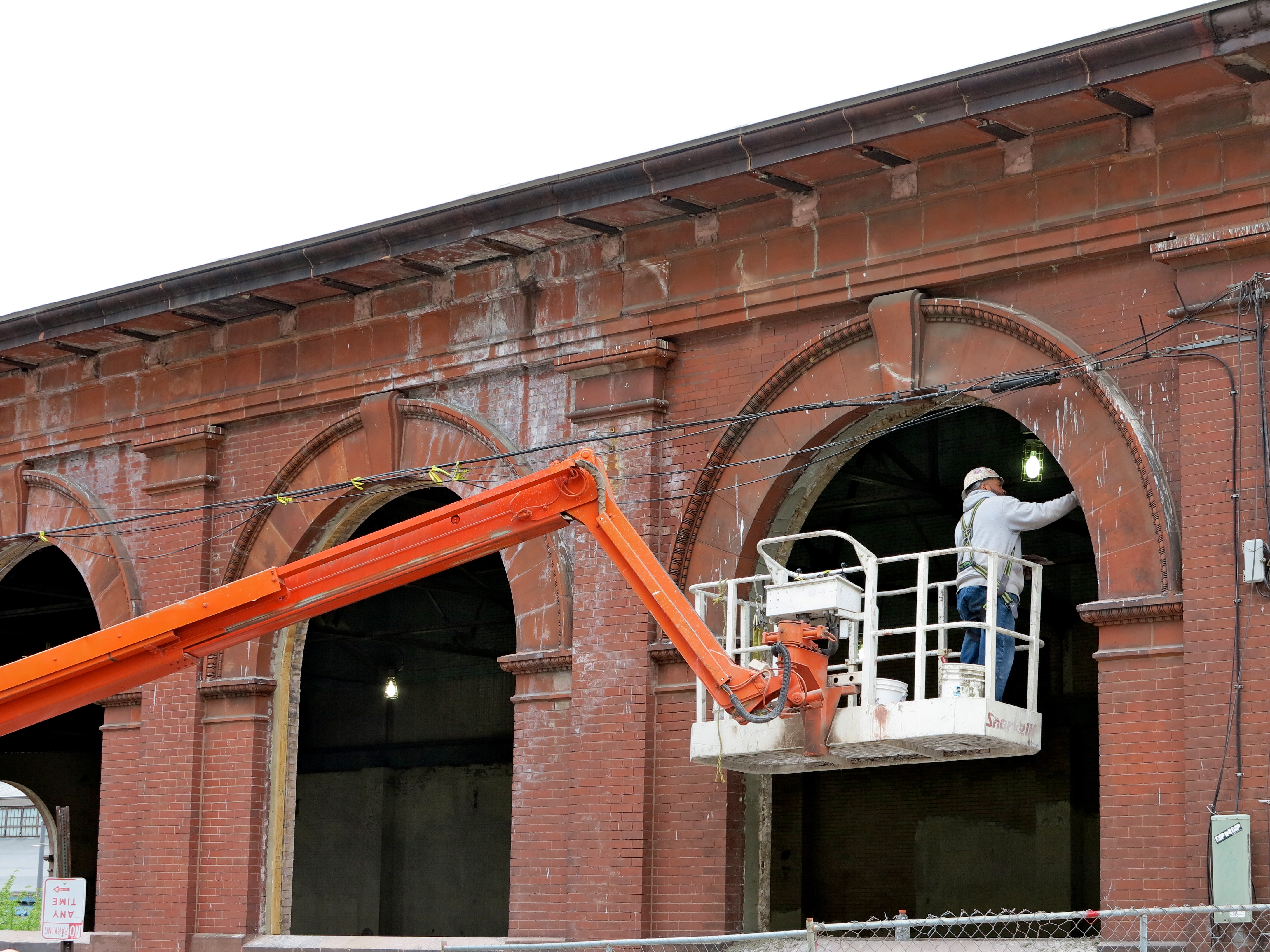 A worker patching an arched masonry window opening along Race Street.