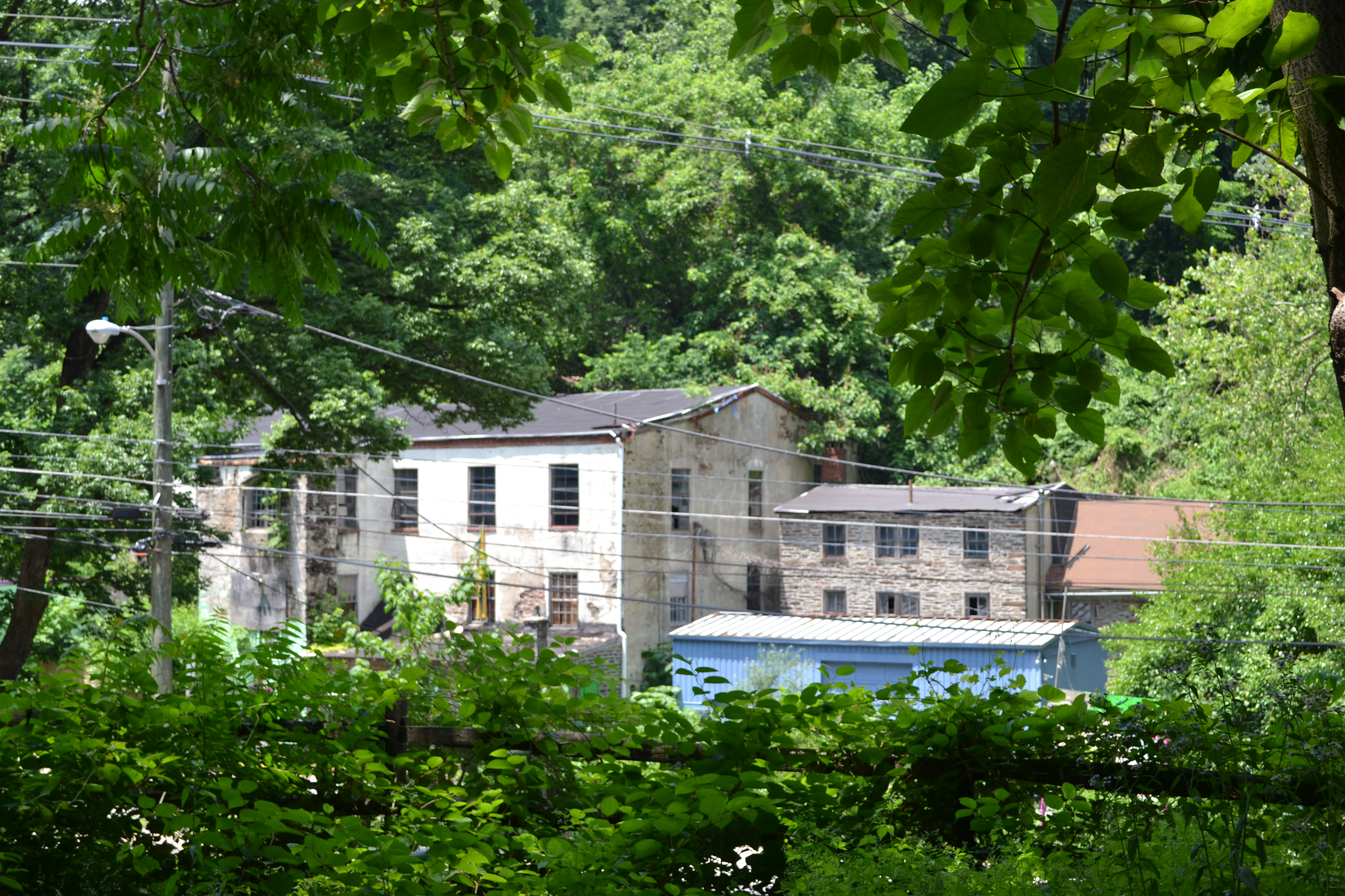 An abandoned mill building stands across from the Rock Hill Road and Belmont Ave end of the trail