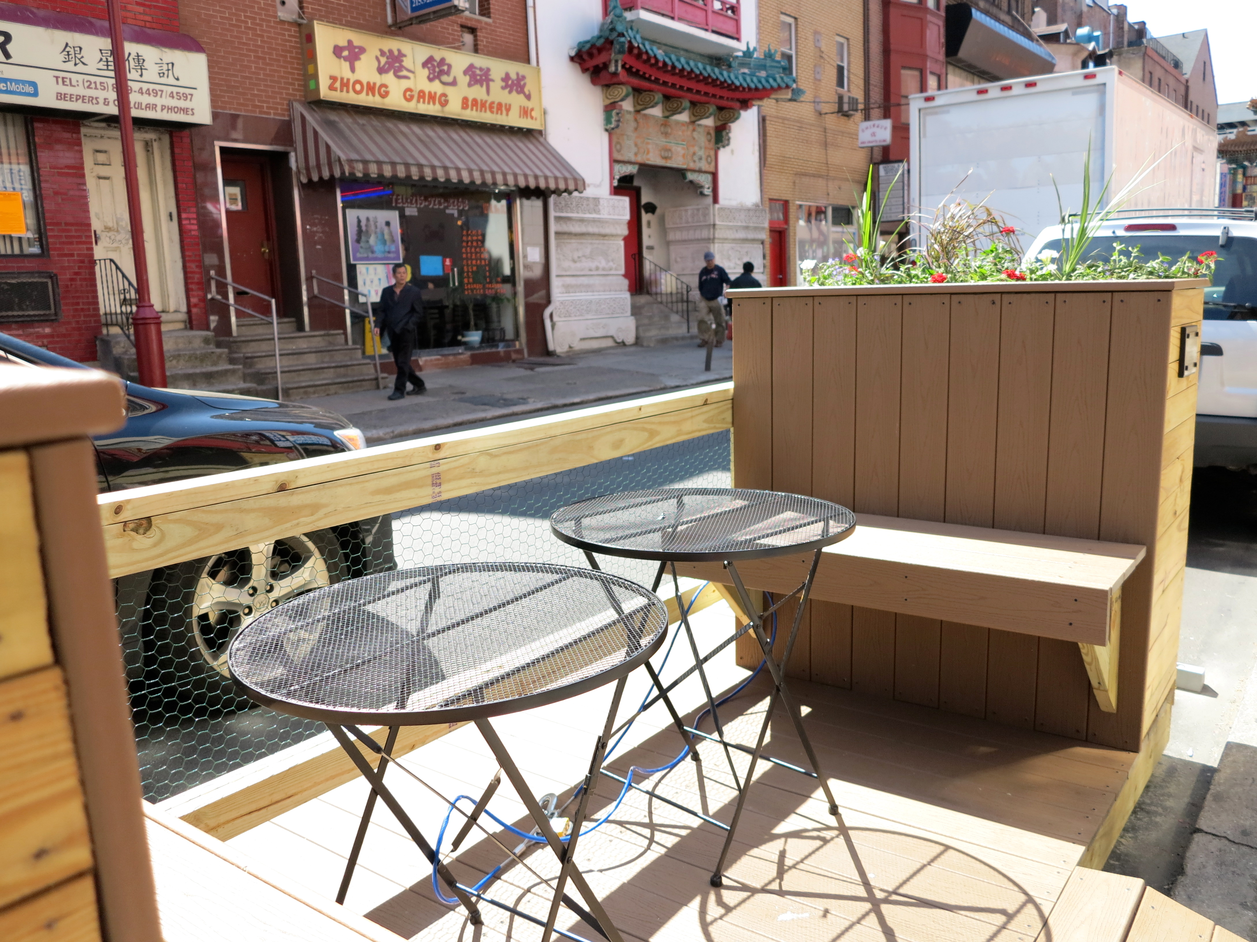 The parklet features built-in benches and two tables.