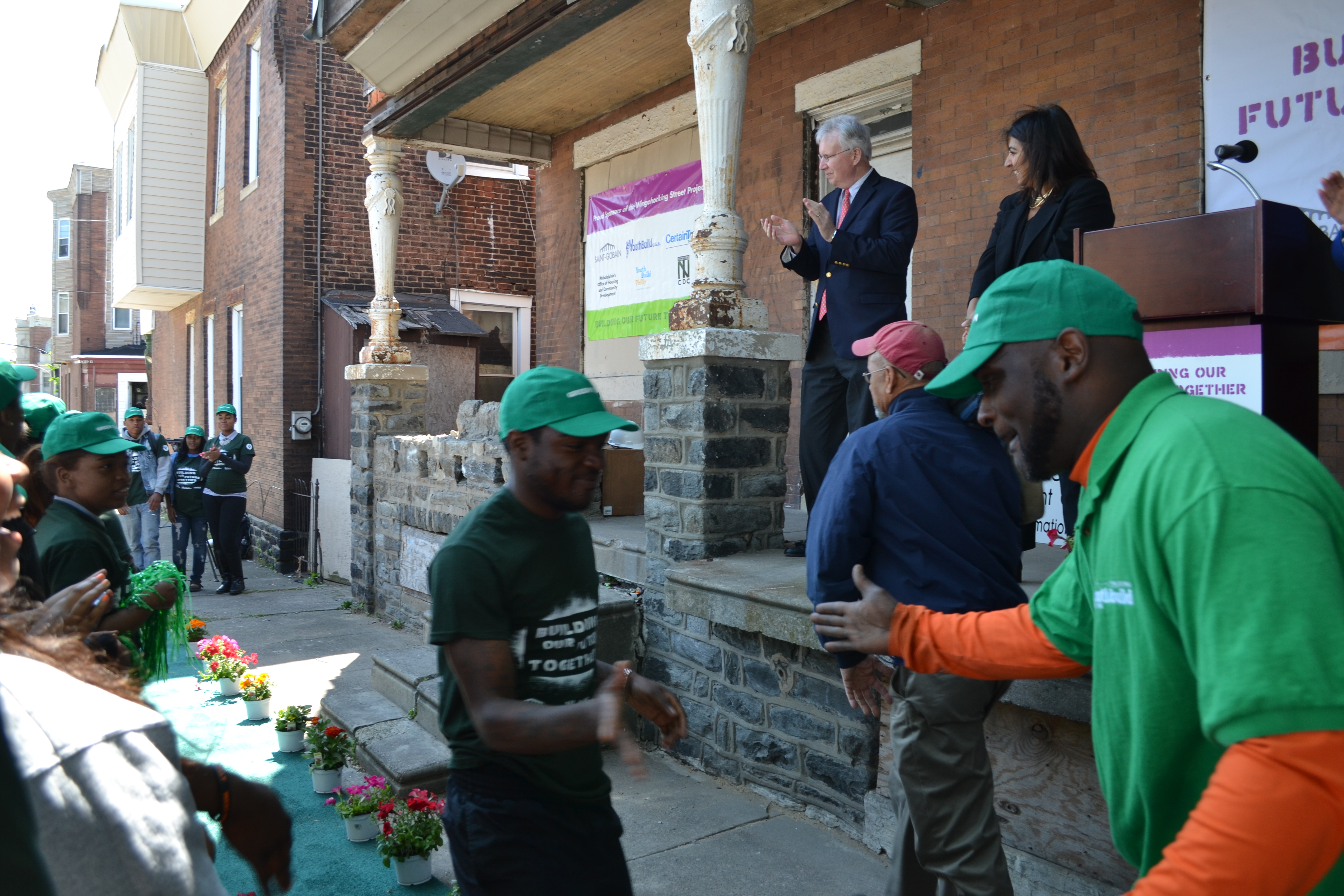 YouthBuild Philadelphia students ran down a green carpet at the groundbreaking