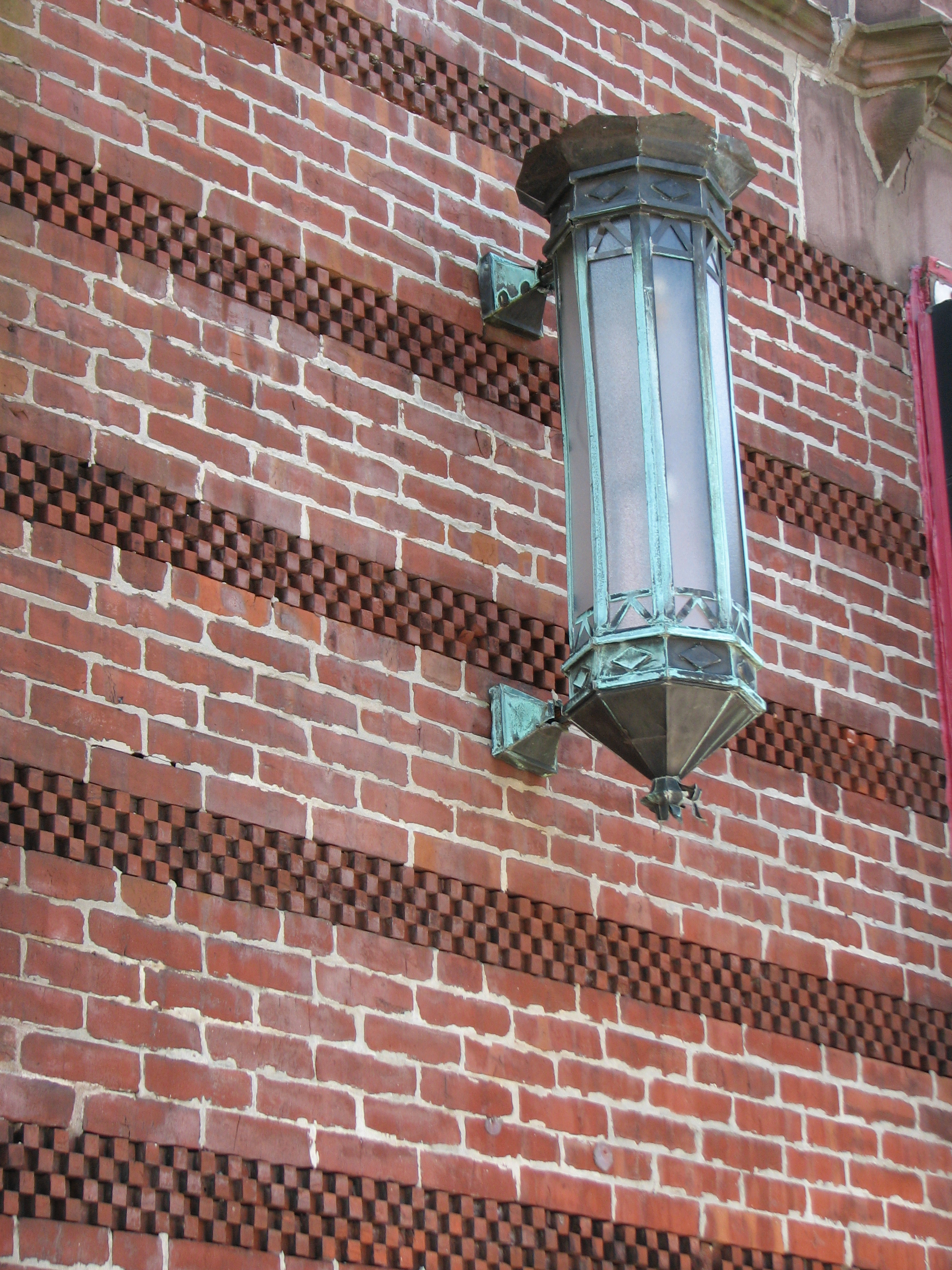 Original lamp fixtures still hang on the decorative brick on either side of the building's entrance.