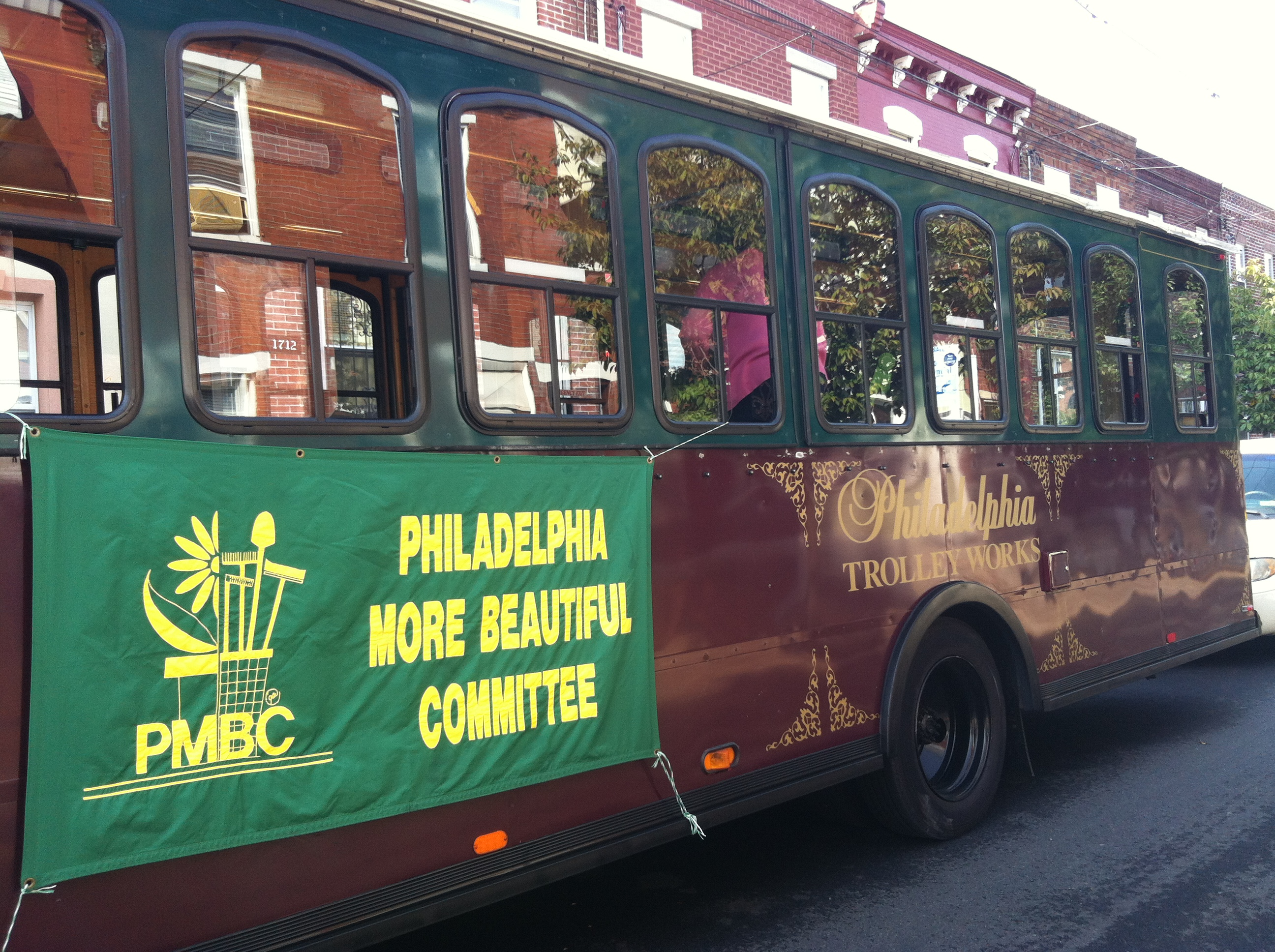 Around 20 citizen judges ride on the Philadelphia More Beautiful Clean Block Contest trolley escorted by police and several city vehicles.