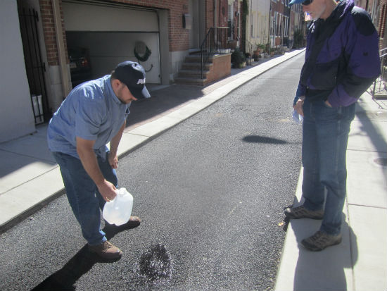 PWD's Pete Reilly demonstrated how water poured directly onto the porous paving on Percy Street seeps into the ground, rather than puddling
