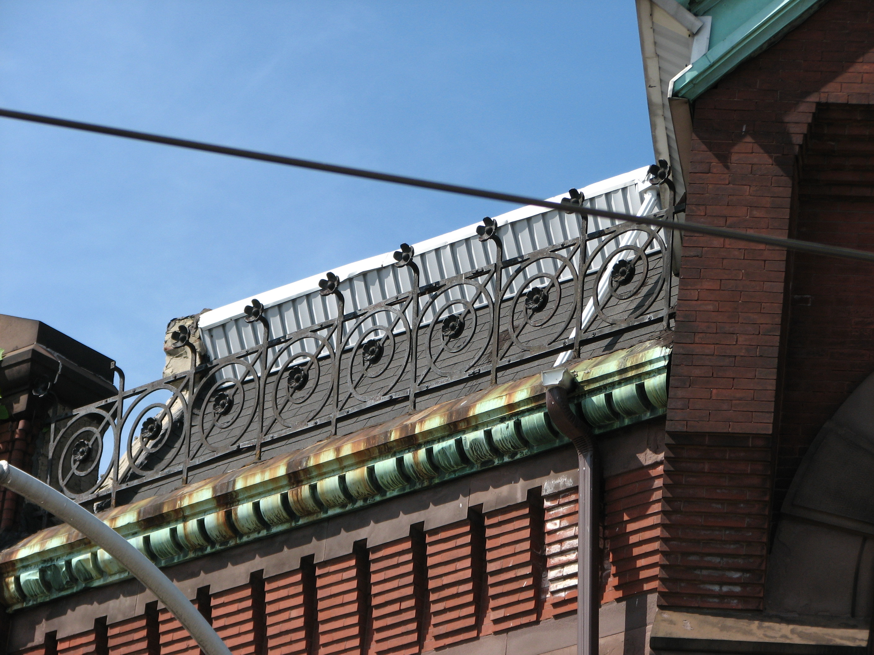 The elaborate ironwork along the roofline, as well as many other features, recall the work of Frank Furness.