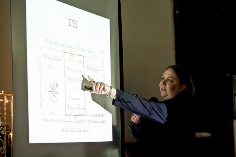 Archaeologist Mary Alfson Tinsman points to slides showing historical maps of Potter's Field at a meeting in late December.