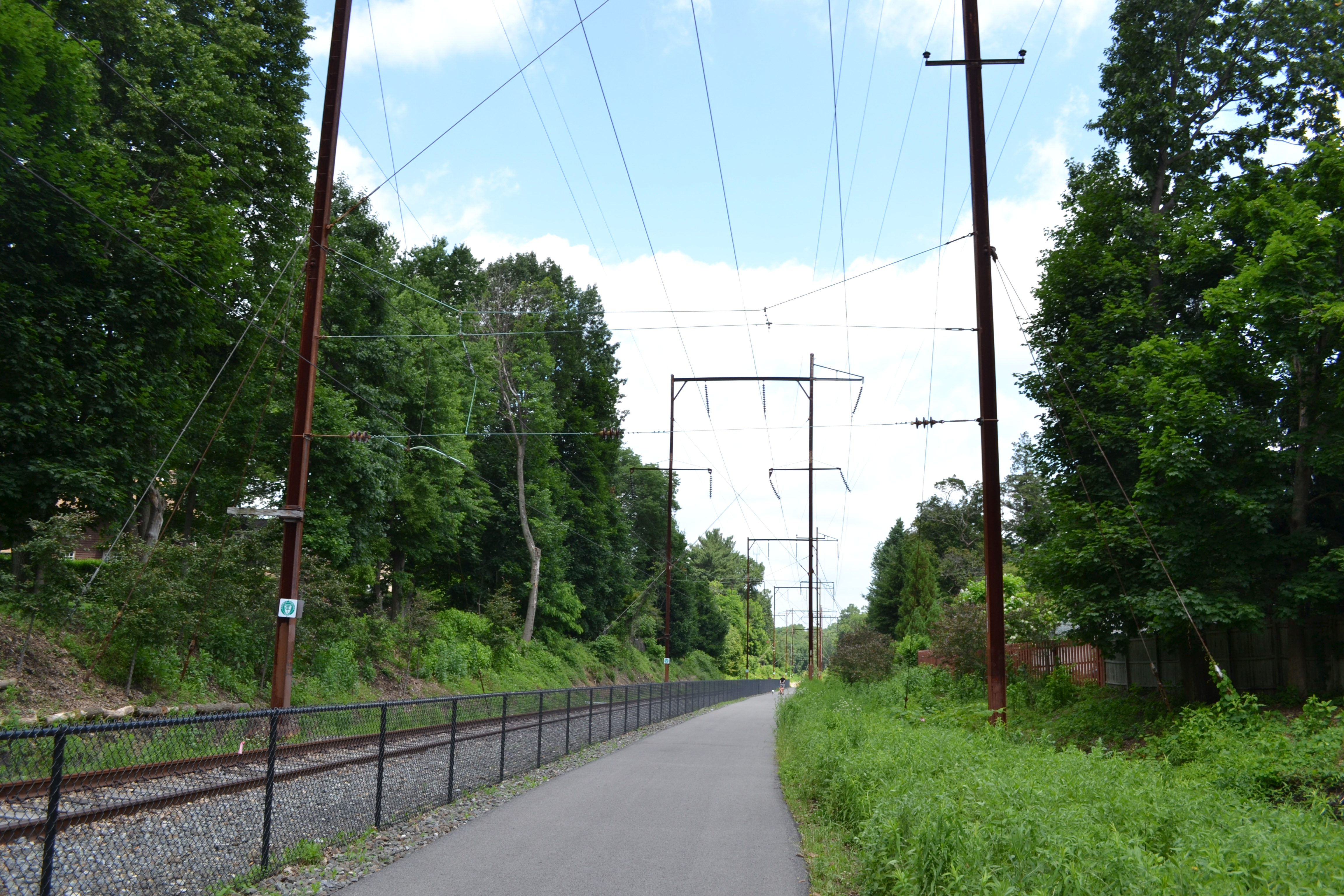 The paved portion of the trail starts alongside an existing segment of tracks