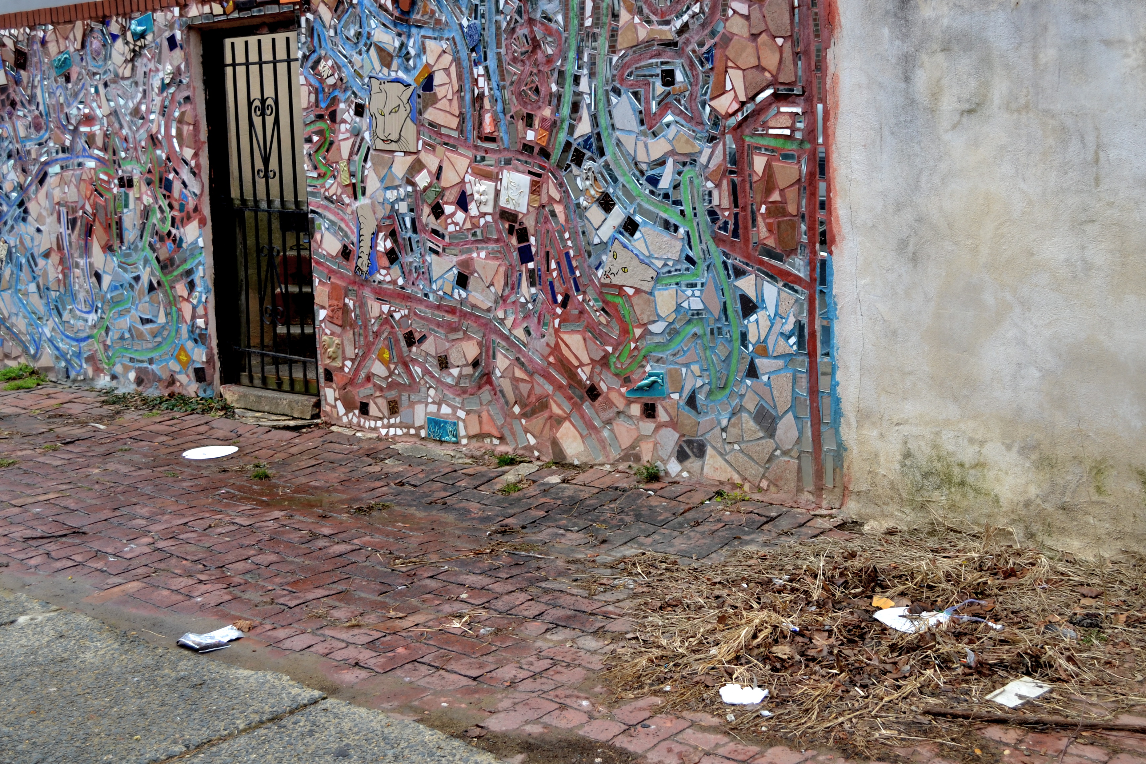 Trash litters the street in front of a South Philly mosaic
