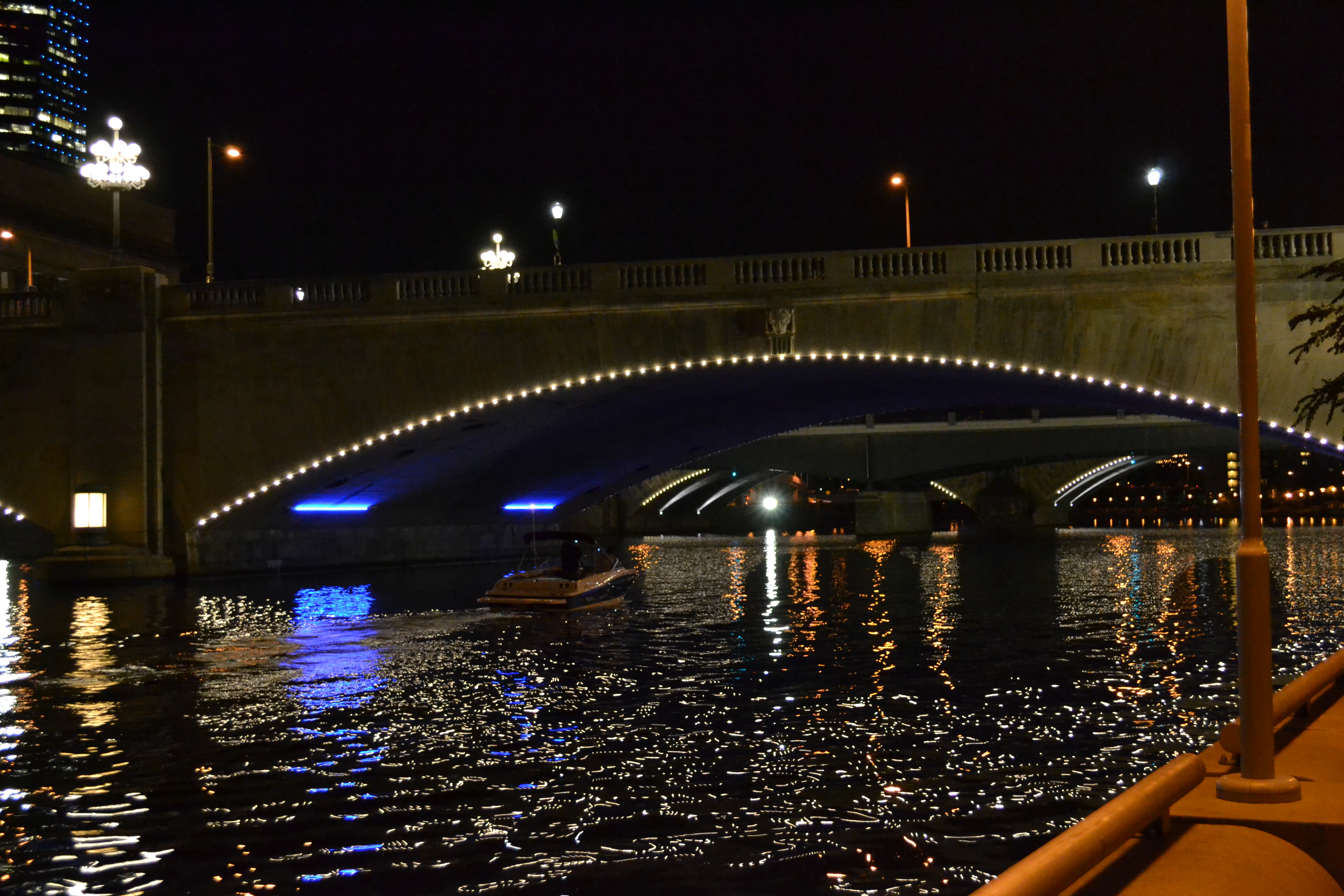A boat cruised beneath the illuminated bridges as the lights danced on the water