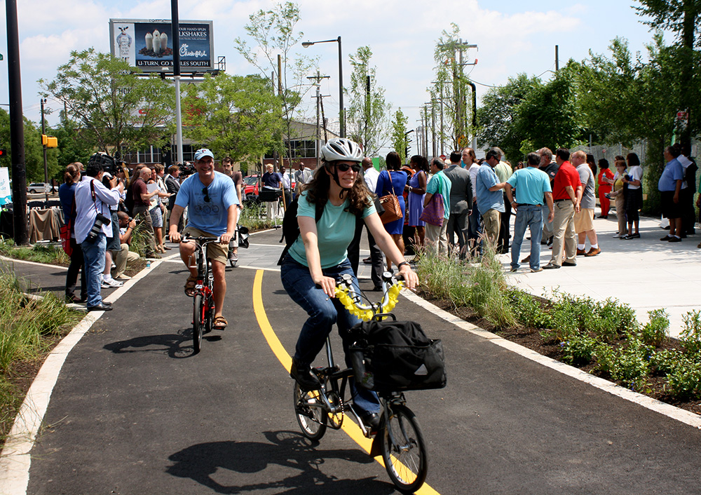 Bikers ride along stormwater tree trenches on Penn Street Trail