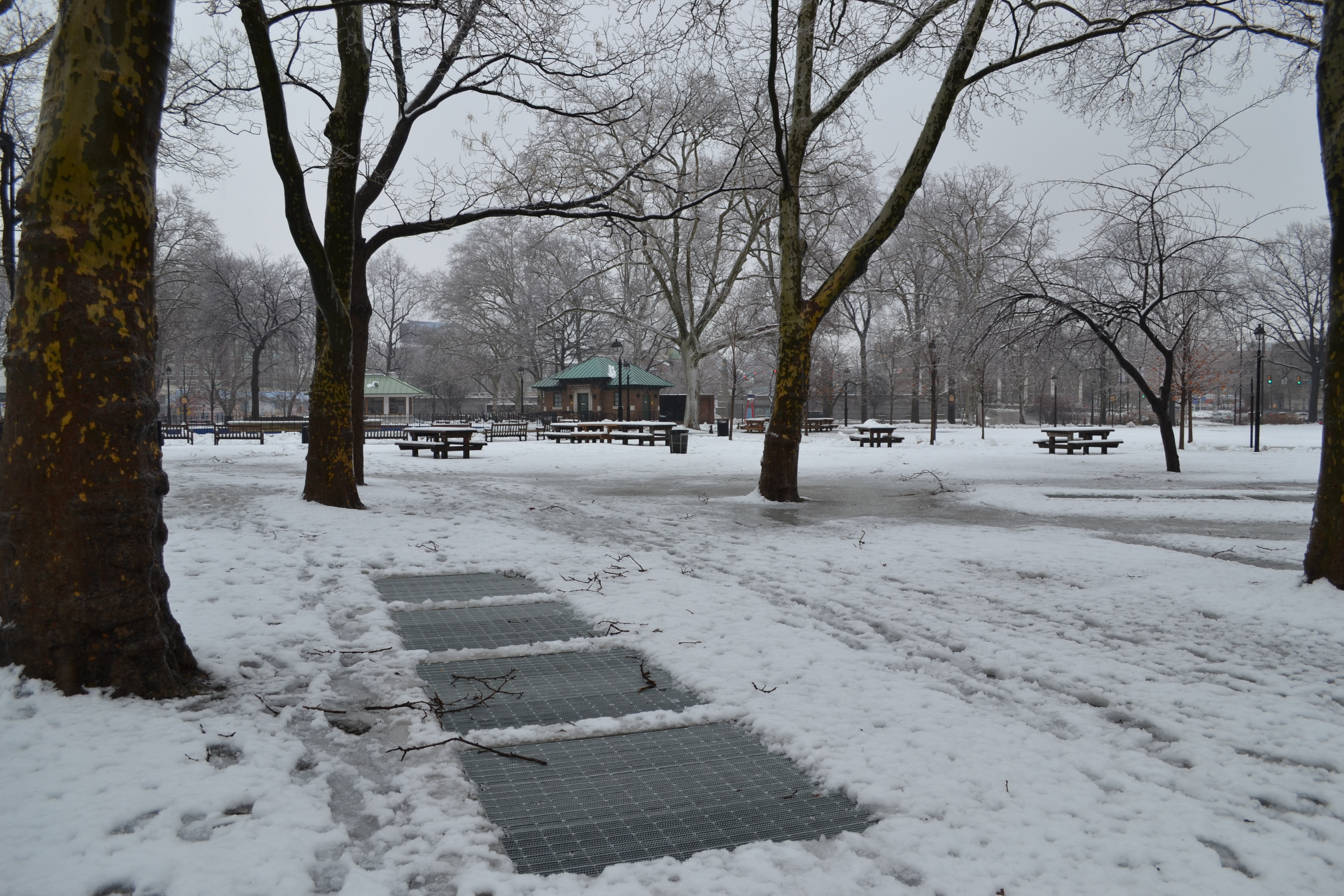 Even in the snow, subway grates betray the station's hiding space beneath the park