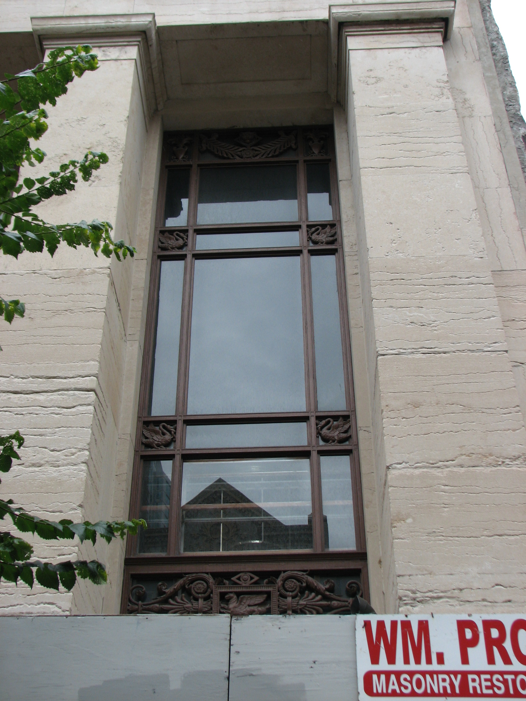 The building's vertical columns are broken by deep-set windows with decorative frames.