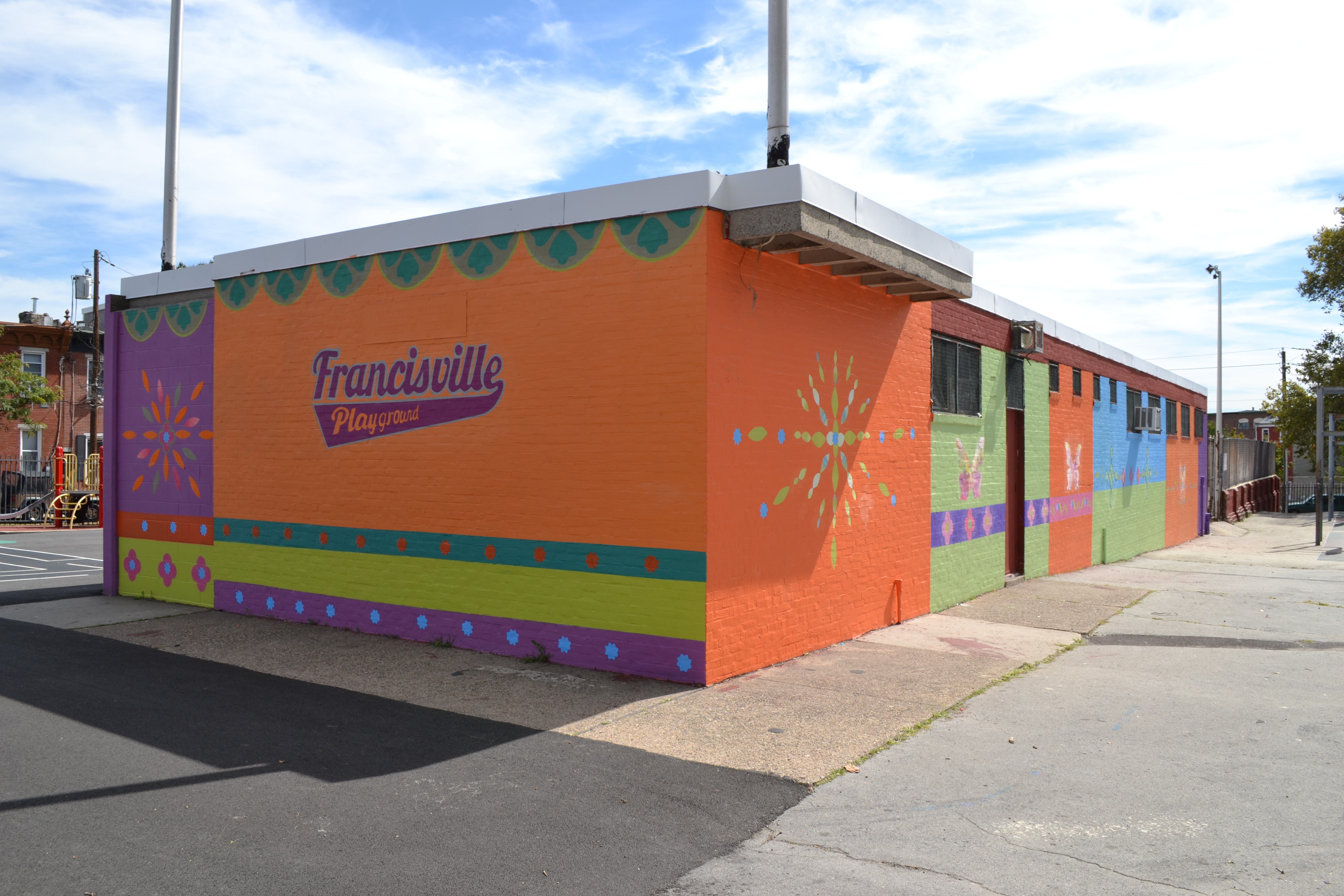 Mural Arts painted a bright mural on the rec center next to the revamped playground