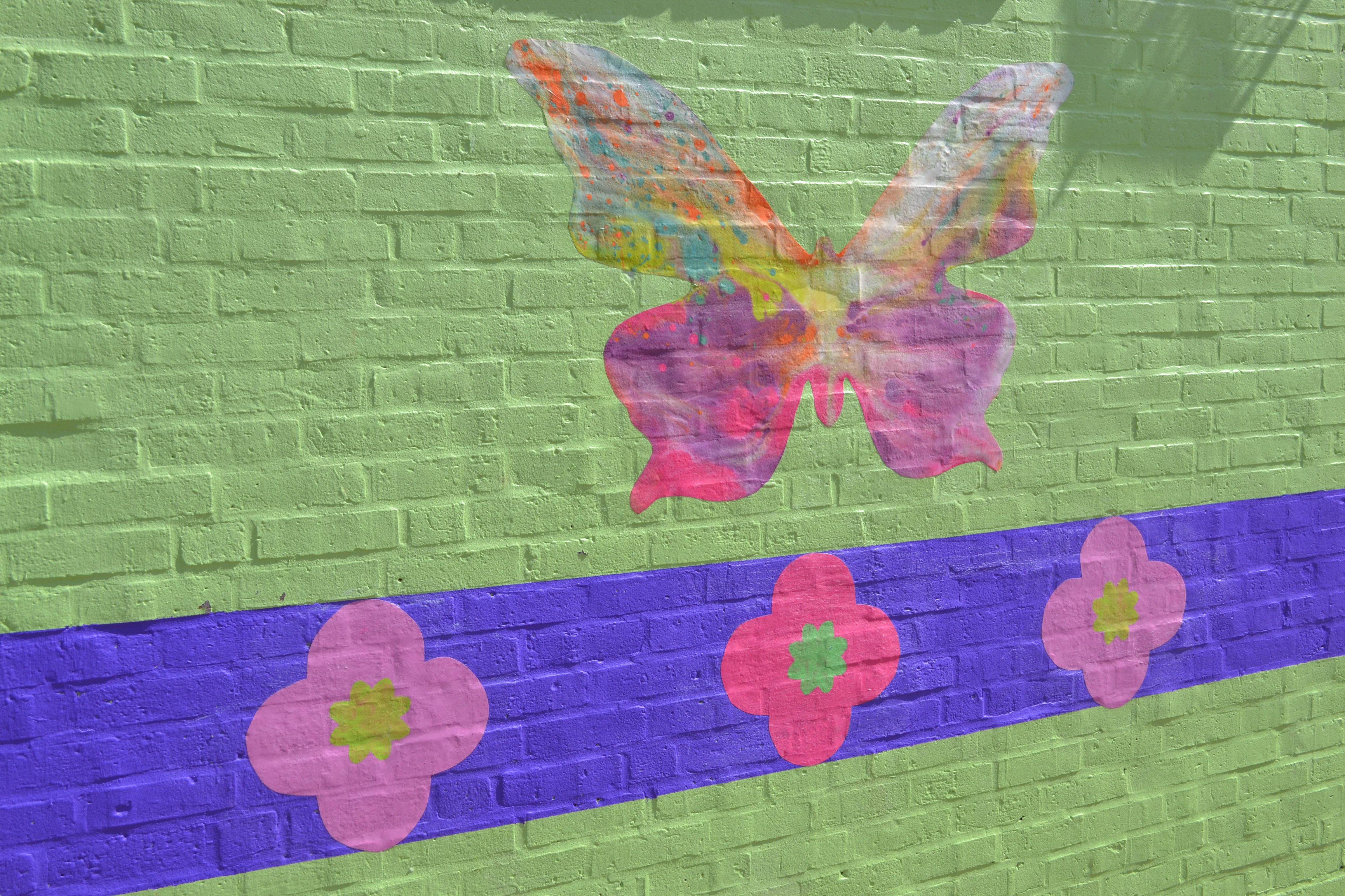 Pre-K students and some summer camp attendees helped paint butterflies on the mural