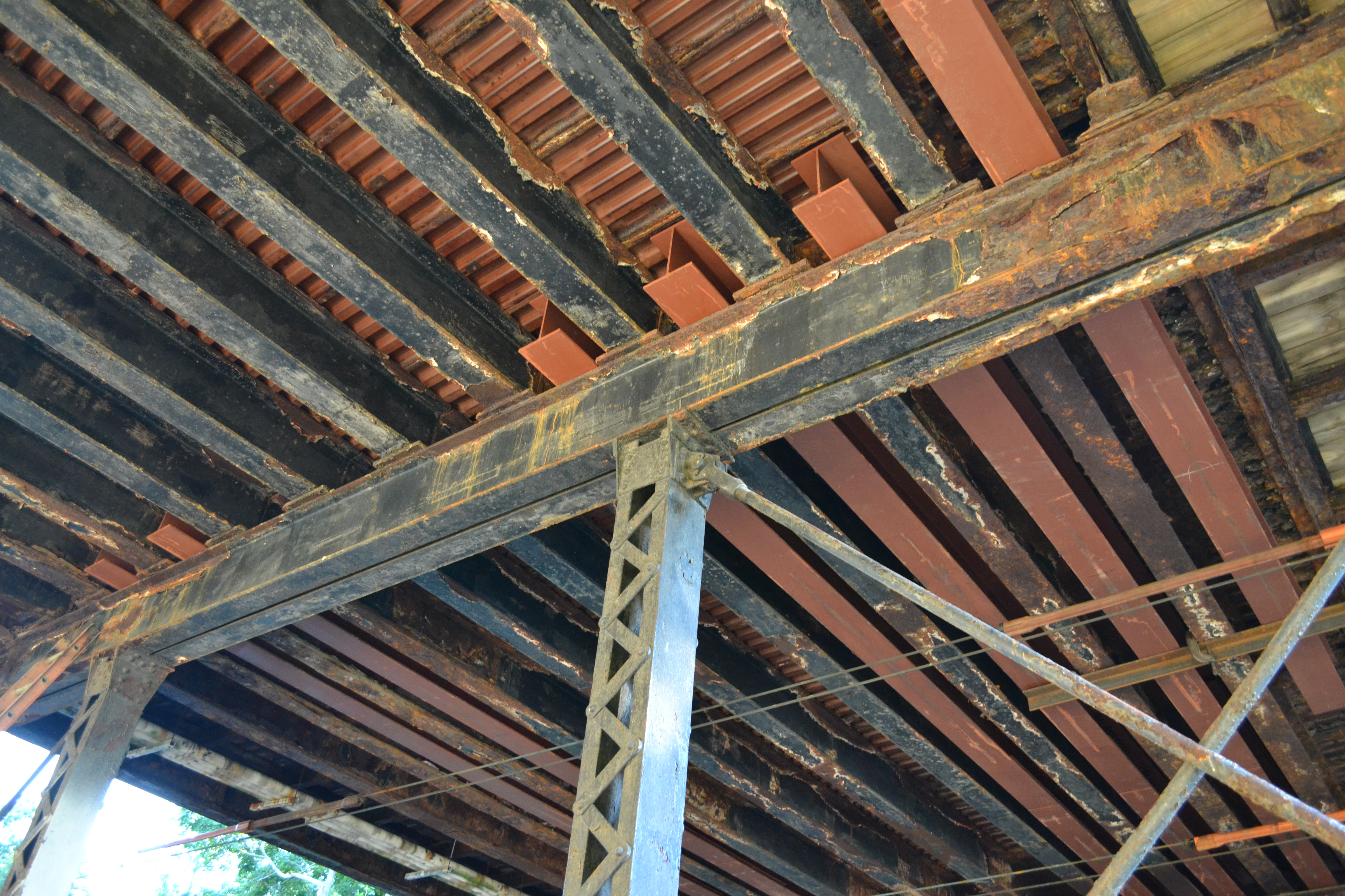 The new beams fit between and reinforce the old, corroded beams