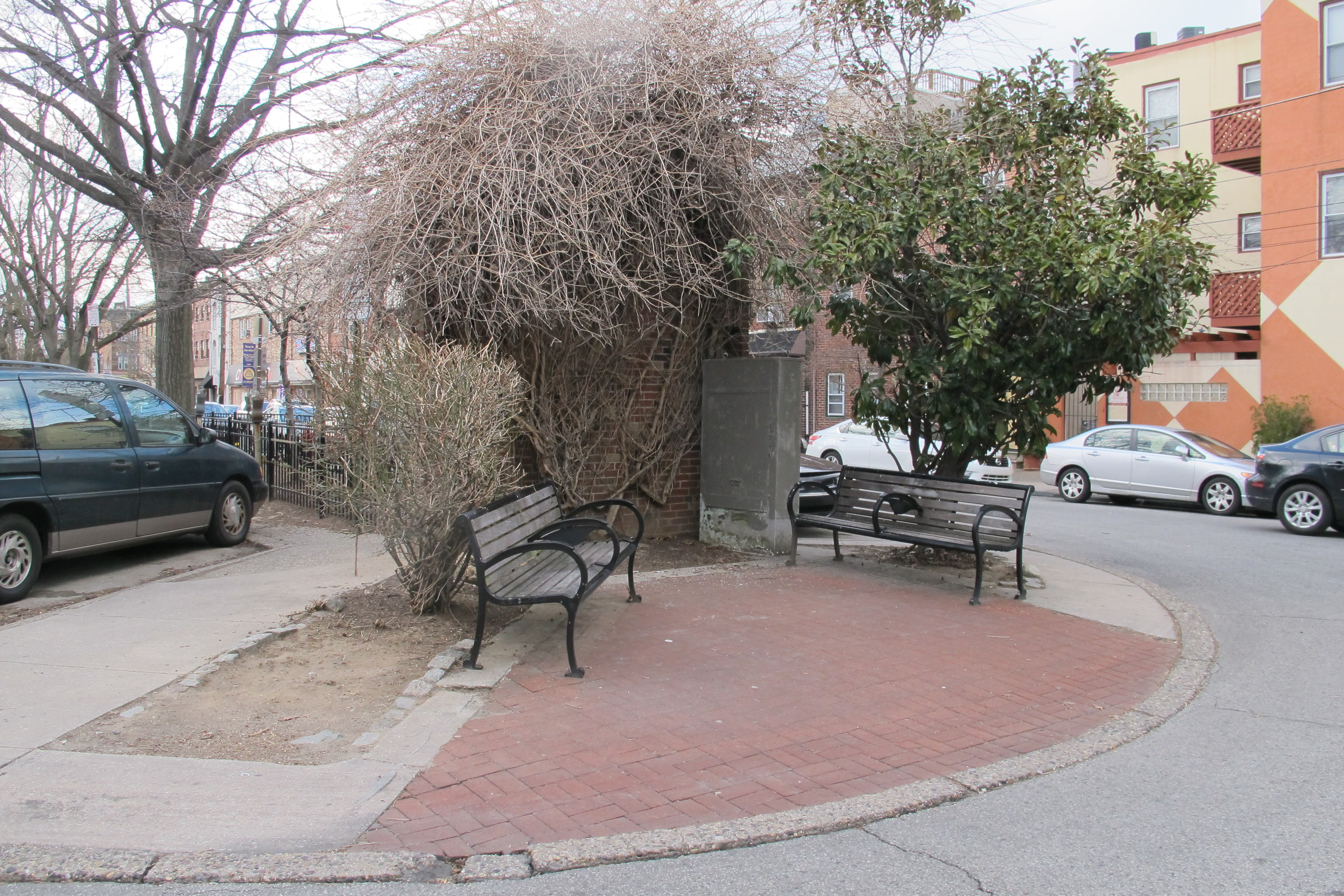 The tired, oddly shaped plaza at 3rd Street features an overgrown brick wall that once had a veterans memorial on it.