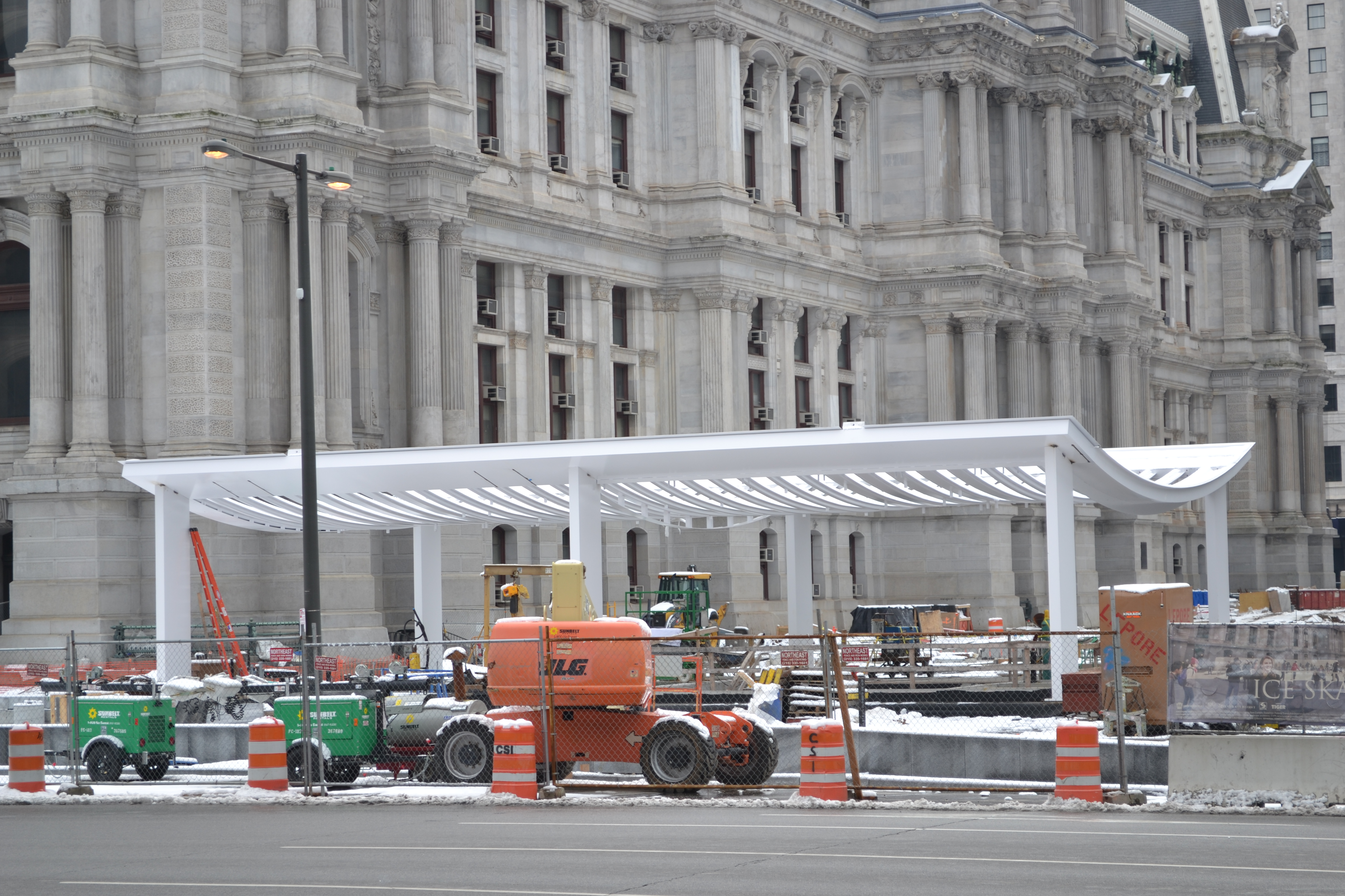The white frame stands out against the gray backdrop of City Hall and the construction site