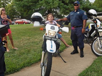 Denise and Marissa Gibson along with an 8th District officer try out a motorcycle at the National Night Out event.