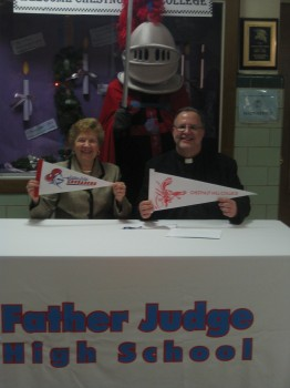 Chestnut Hill College President Sr. Carol Jean Vale, SSJ, and Father Judge High School President Fr. Joe Campellone celebrate their signed agreement with the help of the Father Judge Crusader.