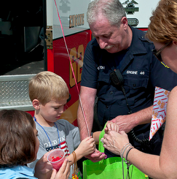Firefighter Stanston helps a young boy with his items from the days event. Photo by George Mai.
