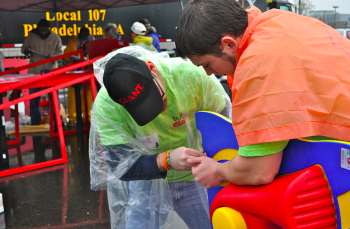 Two Giant employees work in the rain to help assemble Mayfair Memorial Playground. Photo by Kirsten Stamn